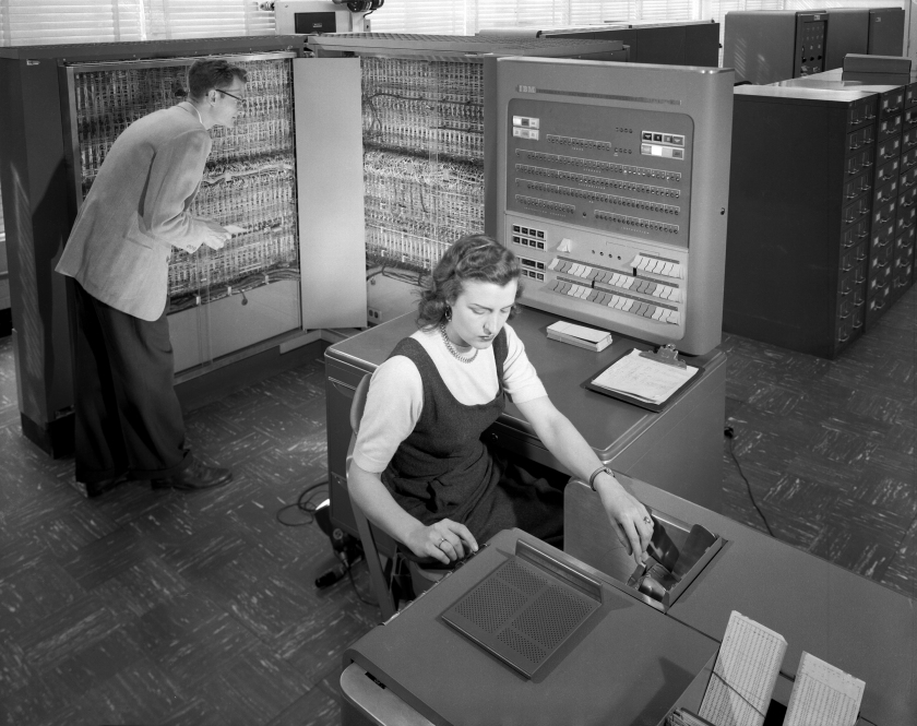 Man and woman shown working with IBM type 704 electronic data processing machine used for making computations for aeronautical research.